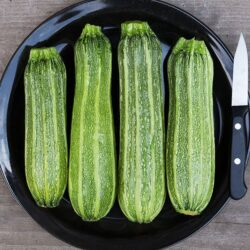 Image of four Costata Romesco Zucchini on a plate next to a paring knife to show scale.