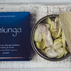Image of the front of a package and an open tin of Artesanos Alalunga Cocochas de Merluza Europea (European Hake Cheeks) in Olive Oil 6/8