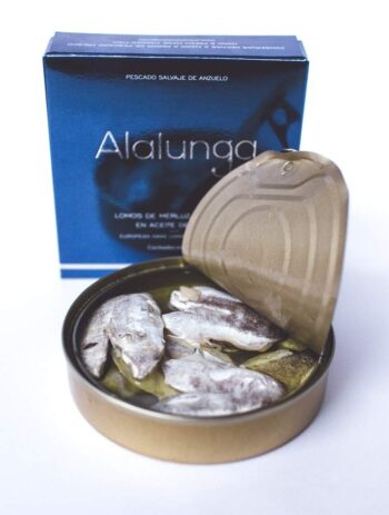 Image of an open tin and the front of a package of Artesanos Alalunga Cocochas de Merluza Europea (European Hake Cheeks) in Olive Oil 6/8