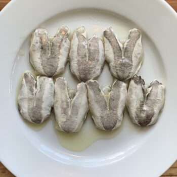 Image of the plated contents of a tin of Artesanos Alalunga Cocochas de Merluza Europea (European Hake Cheeks) in Olive Oil 6/8