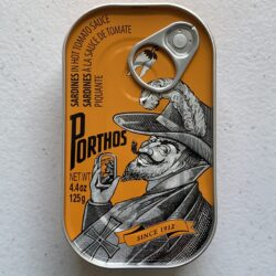 Image of the front of a tin of Porthos Sardines in Hot Tomato Sauce