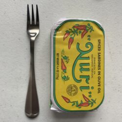 Image of a Cocktail Fork, Choice Midland, Stainless Steel, Medium Weight next to a tin of sardines for scale
