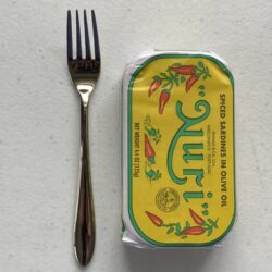 Image of a Cocktail Fork, Acopa Remy, Stainless Steel, Extra Heavy Weight next to a tin of sardines for scale.