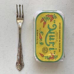 Image of a Cocktail Fork, Walco Discretion, Stainless Steel, Heavy Weight next to a tin of sardines for scale