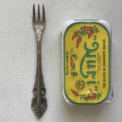 Image of a Cocktail Fork, Walco Classic Baroque (Fieldstone Finish), Extra Heavy Weight next to a tin of sardines for scale.