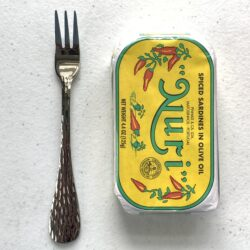 Image of a Cocktail Fork, Acopa Industry, Stainless Steel, Heavy Weight next to a tin of fish for scale